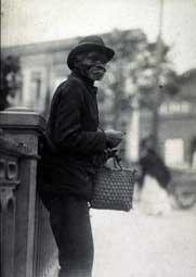 Pastore, Vincenzo. Retrato de homem idoso recostado em grade metálica da rua São João. Trecho da rua São João, em frente ao Bijou Salão. São Paulo. SÃO PAULO / Brasil. 1910 circa.