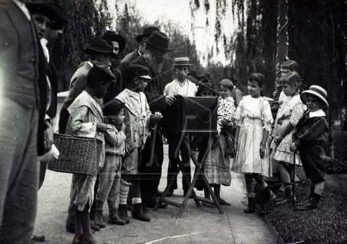 Pastore, Vincenzo. Grupo de pessoas ao redor de realejo, na praça da República. Praça da República. São Paulo. SÃO PAULO / Brasil. 1910 circa.